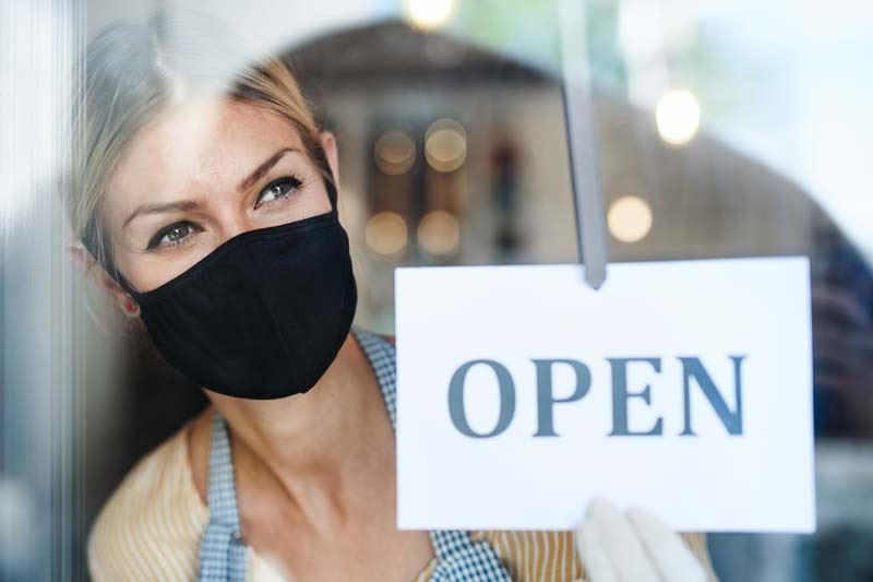 A woman wearing a mask standing by an open sign on a business.