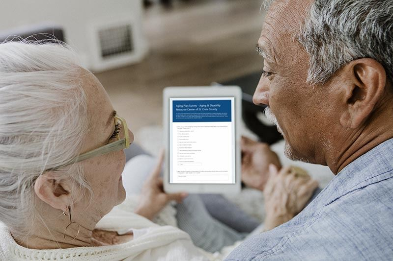 Older adults looking at a digital tablet with the ADRC Aging Survey.
